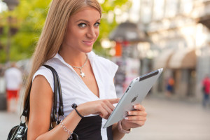 Woman with iPad walking on urban street