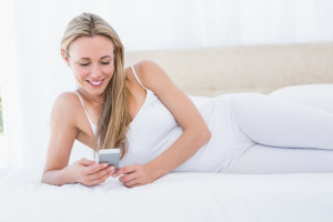 Smiling blonde reading a text